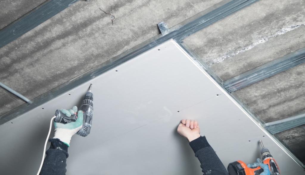 Pracownik montuje podwieszany sufit