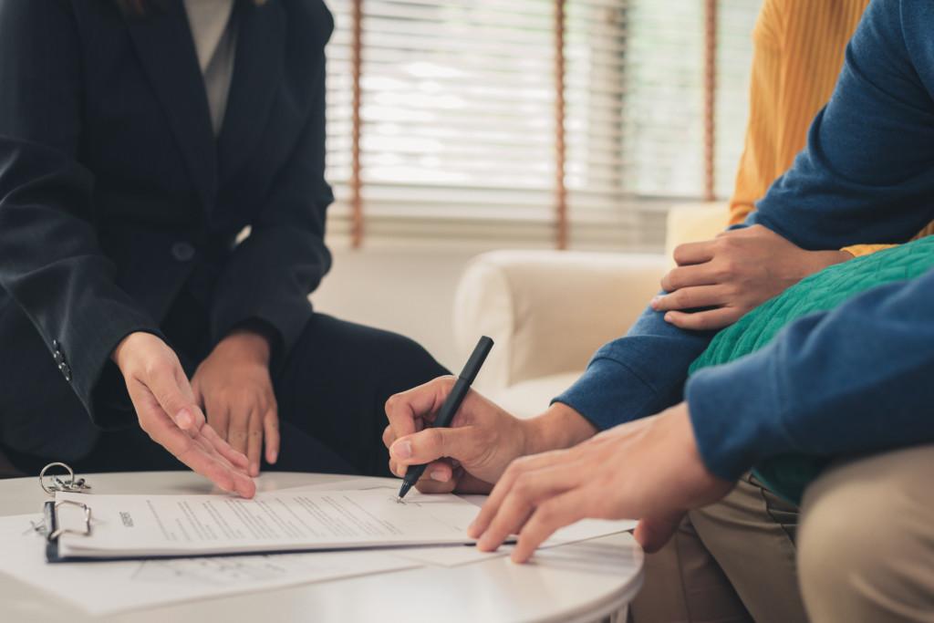 Troje ludzi podpisuje umowę